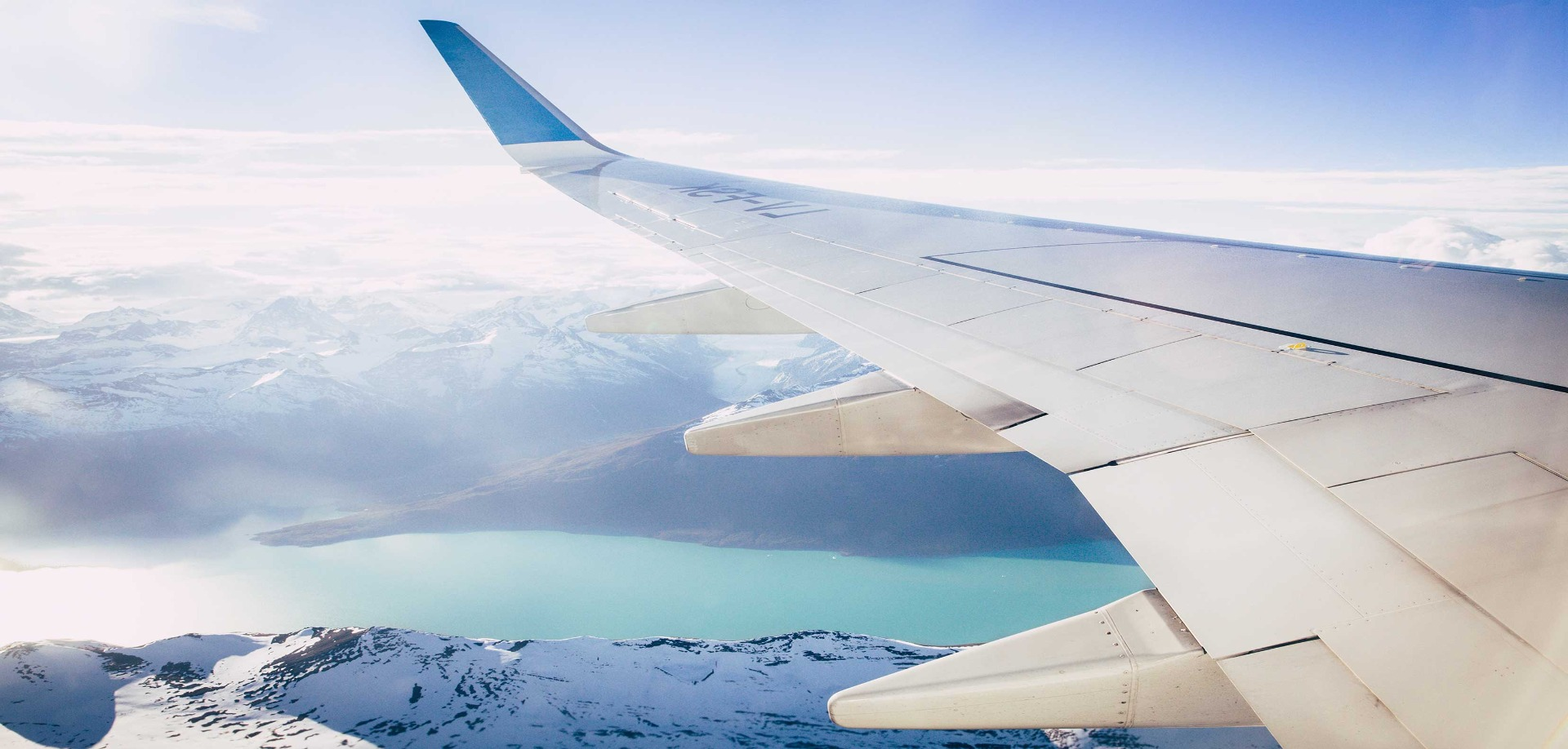 View from an airplane window over the wing out to a landscape of a frozen see and snow covered mountains.